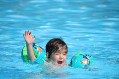 Ένα χαριτωμένο μικρό παιδί στα διογκώσιμα μανίκια που απολαμβάνει το χρόνο του σε μια πισίνα κατά τη διάρκεια ενός καυτού θερινού Στοκ φωτογραφία με δικαίωμα ελεύθερης χρήσης