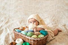 Ένα χαριτωμένο μωρό βρίσκεται σε ένα καλάθι με τη σύγχυση του πλεξίματος των νημάτων Hendmeid των πολύχρωμων νημάτων στοκ εικόνες με δικαίωμα ελεύθερης χρήσης