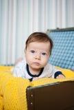 Ένα χαριτωμένο μωρό που βρίσκεται στο κίτρινο πλεκτό περικάλυμμα Στοκ Φωτογραφία