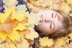 Ένα χαριτωμένο νέο κορίτσι βρίσκεται στο φύλλωμα φθινοπώρου με τις ιδιαίτερες προσοχές, μια ανθοδέσμη των κίτρινων φύλλων φθινοπώ Στοκ Εικόνες