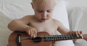 Ένα χαριτωμένο παιδί αγγίζει τις σειρές σε ένα μουσικό όργανο απόθεμα βίντεο