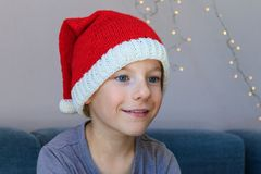 Ένα χαριτωμένο παιδί που φορά ένα πλεκτό καπέλο Santa Σχέδιο Χριστουγέννων Enchantment, έκπληξη, κατάπληξη, έκφραση κατάπληξης στοκ φωτογραφία