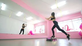 Ένα χαριτωμένο brunette εκτελεί τις ασκήσεις ικανότητας ικανότητας μπροστά από έναν καθρέφτη Αδυνάτισμα στη γυμναστική Υγιής τρόπ απόθεμα βίντεο