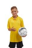 Ένα χαρούμενο αγόρι με μια σφαίρα ποδοσφαίρου που απομονώνεται πέρα από το άσπρο υπόβαθρο Ένας έφηβος sportswear Ενεργός έννοια τ Στοκ Εικόνα