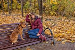 Ένα χαρούμενο κοκκινομάλλες κορίτσι κάθεται σε έναν πάγκο και τα όνειρα μαζί με ένα κόκκινο σκυλί στοκ φωτογραφία