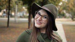 Ένα χαρούμενο κορίτσι στο πάρκο το φθινόπωρο Συγκίνηση, ένα κορίτσι σε ένα καπέλο και γυαλιά απόθεμα βίντεο