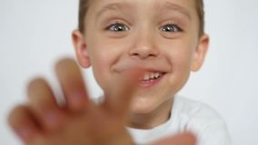 Ένα χαρούμενο παιδί χαμογελά και τραβά το χέρι του προς τα εμπρός στη κάμερα απόθεμα βίντεο