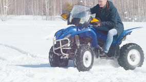 Ένα χειμερινό δάσος στο φως της ημέρας Κρύος καιρός Ένα ενήλικο άτομο που οδηγά ένα μεγάλο μπλε όχημα για το χιόνι απόθεμα βίντεο