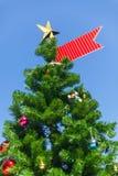Ένα χριστουγεννιάτικο δέντρο έστεψε με έναν δέντρο-άριστο αστεριών και μια κόκκινη κορδέλλα Στοκ Φωτογραφίες