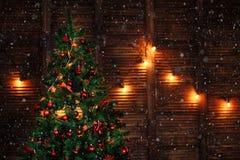 Ένα χριστουγεννιάτικο δέντρο που διακοσμείται με τις διακοσμήσεις παιχνιδιών διακοσμεί την κόκκινη γιρλάντα στον ξύλινο καφετή το στοκ φωτογραφίες με δικαίωμα ελεύθερης χρήσης