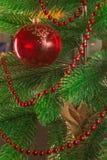 Ένα χριστουγεννιάτικο δέντρο που διακοσμείται με τις χάντρες και μια κόκκινη σφαίρα γυαλιού Μια διαφανής νέα σφαίρα έτους ` s όμο Στοκ Εικόνες