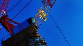 Ένα χρονικό σφάλμα της κίνησης των γερανών πίσω από το μπλε ουρανό στο ζουμ κινηματογραφήσεων σε πρώτο πλάνο του Τόκιο φιλμ μικρού μήκους