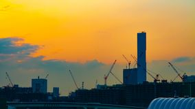 Ένα χρονικό σφάλμα της κίνησης των γερανών στην κατώτερη κατασκευή στο Τόκιο στην ευρεία πυροβοληθείσα κλίση σούρουπου φιλμ μικρού μήκους