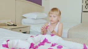 Ένα 6χρονο κορίτσι με ένα βραχιόλι ξενοδοχείων σε ετοιμότητα της παίζει με τα πέταλα λουλουδιών Σε την το κρεβάτι είναι μια καρδι φιλμ μικρού μήκους