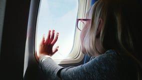 Ένα 6χρονο κορίτσι με τα θεάματα κάθεται σε ένα αεροπλάνο, φαίνεται έξω το παράθυρο Το χέρι της πιέζεται στην παραφωτίδα - ένας ε απόθεμα βίντεο