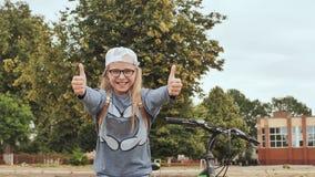 Ένα 11χρονο κορίτσι παρουσιάζει αντίχειρές της σε μια καλή διάθεση δίπλα στο ποδήλατό της το καλοκαίρι φιλμ μικρού μήκους