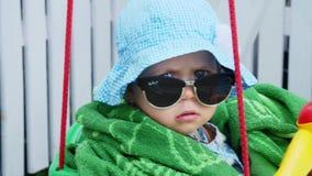 Ένα 1χρονο κορίτσι σε έναν Παναμά και τα γυαλιά ηλίου, όπως μια σημαντική κυρία, κάθονται στην ταλάντευση και την ταλάντευση παιδ απόθεμα βίντεο