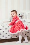 Ένα 1χρονο κορίτσι σε ένα κόκκινο φόρεμα λαμβάνει τα πρώτα μέτρα της που κρατούν επάνω στο κρεβάτι στο δωμάτιο Στοκ εικόνα με δικαίωμα ελεύθερης χρήσης