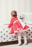 Ένα 1χρονο κορίτσι σε ένα κόκκινο φόρεμα λαμβάνει τα πρώτα μέτρα της που κρατούν επάνω στο κρεβάτι στο δωμάτιο Στοκ εικόνες με δικαίωμα ελεύθερης χρήσης