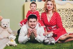 Ένα 1χρονο κορίτσι σε ένα κόκκινο φόρεμα κάθεται μια κουβέρτα με τους γονείς της και με τα παιχνίδια βελούδου στο δωμάτιο Στοκ Εικόνα