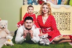 Ένα 1χρονο κορίτσι σε ένα κόκκινο φόρεμα κάθεται μια κουβέρτα με τους γονείς της και με τα παιχνίδια βελούδου στο δωμάτιο Στοκ Φωτογραφίες