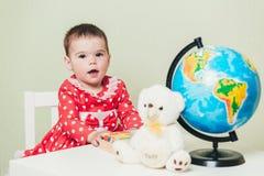 Ένα 1χρονο κορίτσι σε ένα κόκκινο φόρεμα κάθεται σε έναν πίνακα με ένα βιβλίο, μια σφαίρα και μια teddy αρκούδα Στοκ Εικόνες