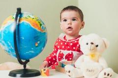 Ένα 1χρονο κορίτσι σε ένα κόκκινο φόρεμα κάθεται σε έναν πίνακα με ένα βιβλίο, μια σφαίρα και μια teddy αρκούδα Στοκ Φωτογραφίες