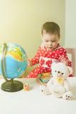 Ένα 1χρονο κορίτσι σε ένα κόκκινο φόρεμα κάθεται σε έναν πίνακα με ένα βιβλίο, μια σφαίρα και μια teddy αρκούδα Στοκ Εικόνα