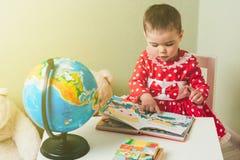 Ένα 1χρονο κορίτσι σε ένα κόκκινο φόρεμα κάθεται σε έναν πίνακα με ένα βιβλίο, μια σφαίρα και μια teddy αρκούδα Στοκ Φωτογραφία