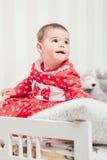 Ένα 1χρονο κορίτσι σε ένα κόκκινο φόρεμα κάθεται σε ένα κρεβάτι σε ένα δωμάτιο Στοκ Εικόνες