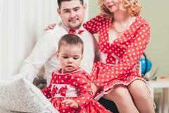 Ένα 1χρονο κορίτσι σε ένα κόκκινο φόρεμα κάθεται σε ένα κρεβάτι σε ένα δωμάτιο με τους γονείς της Στοκ φωτογραφία με δικαίωμα ελεύθερης χρήσης