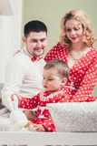 Ένα 1χρονο κορίτσι σε ένα κόκκινο φόρεμα κάθεται σε ένα κρεβάτι σε ένα δωμάτιο με τους γονείς της Στοκ φωτογραφίες με δικαίωμα ελεύθερης χρήσης