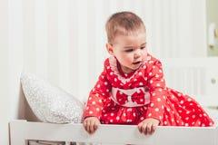 Ένα 1χρονο κορίτσι σε ένα κόκκινο φόρεμα κάθεται σε ένα κρεβάτι σε ένα δωμάτιο Στοκ εικόνα με δικαίωμα ελεύθερης χρήσης