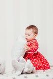 Ένα 1χρονο κορίτσι σε ένα κόκκινο φόρεμα κάθεται σε ένα κρεβάτι σε ένα δωμάτιο Στοκ εικόνες με δικαίωμα ελεύθερης χρήσης