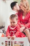 Ένα 1χρονο κορίτσι σε ένα κόκκινο φόρεμα κάθεται σε ένα κρεβάτι σε ένα δωμάτιο με τους γονείς της Στοκ Φωτογραφία