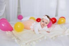 Ένα 1χρονο κορίτσι σε μια ρόδινη πολύβλαστη φούστα σέρνεται σε ένα κρεβάτι με ένα ρόδινο καρό Οι γονείς έντυσαν υπέροχα το μωρό Στοκ εικόνες με δικαίωμα ελεύθερης χρήσης
