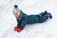Ένα 4χρονο παιδί, ένα αγόρι, οδηγά το στομάχι του από έναν λόφο και γελά στοκ εικόνες