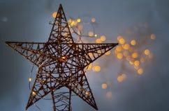 Ένα χρυσό αστέρι φιαγμένο από καλώδιο με τα κίτρινα φω'τα στο υπόβαθρο στοκ εικόνα