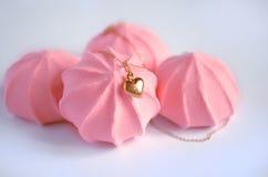 Ένα χρυσό κρεμαστό κόσμημα καρδιών στο ρόδινο υπόβαθρο μαρεγκών φραουλών στοκ φωτογραφία με δικαίωμα ελεύθερης χρήσης