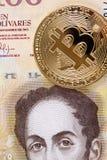 Ένα χρυσό bitcoin ενάντια σε ένα της Βενεζουέλας Bolivares τραπεζογραμμάτιο 100 στοκ εικόνες με δικαίωμα ελεύθερης χρήσης