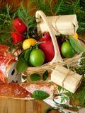 Ένα ψάθινο καλάθι που γεμίζουν με τα φρούτα που περιβάλλονται από τα παρόντα πεδία και τα εργαλεία για το τύλιγμα δώρων Στοκ Φωτογραφία