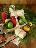 Ένα ψάθινο καλάθι που γεμίζουν με τα φρούτα που περιβάλλονται από τα παρόντα πεδία και τα εργαλεία για το τύλιγμα δώρων Στοκ φωτογραφία με δικαίωμα ελεύθερης χρήσης