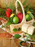 Ένα ψάθινο καλάθι που γεμίζουν με τα φρούτα που περιβάλλονται από τα παρόντα πεδία και τα εργαλεία για το τύλιγμα δώρων Στοκ Εικόνα