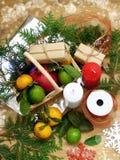 Ένα ψάθινο καλάθι που γεμίζουν με τα φρούτα που περιβάλλονται από τα παρόντα πεδία και τα εργαλεία για το τύλιγμα δώρων Στοκ Εικόνες