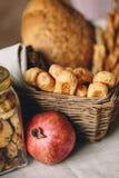 Ένα ψάθινο καλάθι με το ψωμί, ένα βάζο γυαλιού με τα μπισκότα και ένα ρόδι Στοκ Φωτογραφία
