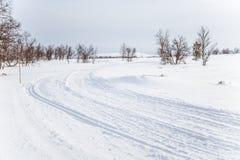 Ένα όμορφο άσπρο τοπίο μιας χιονώδους χειμερινής ημέρας με τις διαδρομές για το όχημα για το χιόνι ή το έλκηθρο σκυλιών Στοκ εικόνες με δικαίωμα ελεύθερης χρήσης