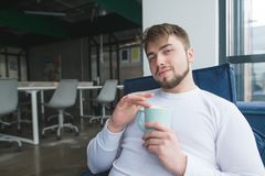 Ένα όμορφο άτομο κάθεται στο γραφείο με ένα φλιτζάνι του καφέ στα χέρια του και χαμογελά στοκ φωτογραφία με δικαίωμα ελεύθερης χρήσης