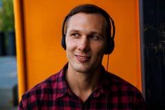 Ένα όμορφο άτομο που απολαμβάνει τη μουσική μέσω των ακουστικών στοκ εικόνες