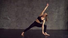 Ένα όμορφο, έξυπνο, αθλητικό κορίτσι κάνει τις ασκήσεις γιόγκας σε μια γυμναστική στο ύφος σοφιτών, με το φυσικό φως από τα μεγάλ απόθεμα βίντεο