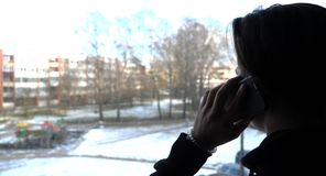 Ένα όμορφο αγόρι ένας έφηβος φαίνεται έξω το παράθυρο στην οδό με ένα τηλέφωνο στο χέρι του Στοκ Φωτογραφία